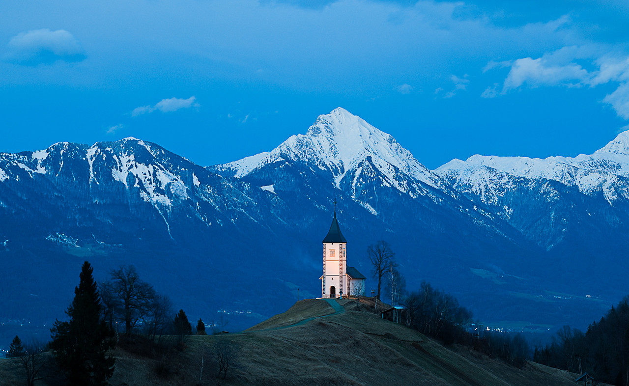 The Church of St. Primoz in Jamnik, Slovenia taken at dusk in the winter and illuminated by floodlights